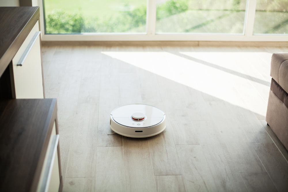 round white floor robot vacuum cleaning a wood floor close to a window
