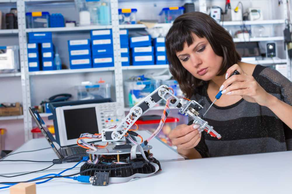 Young woman experimenting with a robotics kit as a hobby