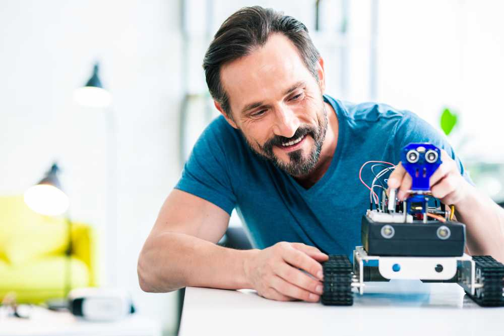 Cheerful adult smiling man adjusting his robotic hobby device while sitting at the table